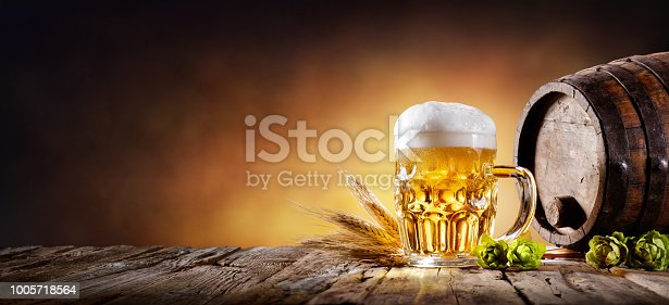 istock Beer Mug With Wheat And Hops In Cellar With Barrel 1005718564