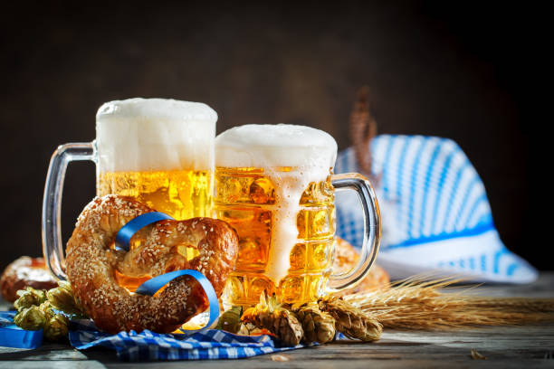 beer mugs and pretzels on a wooden table. oktoberfest. beer festival. - oktoberfest stock pictures, royalty-free photos & images