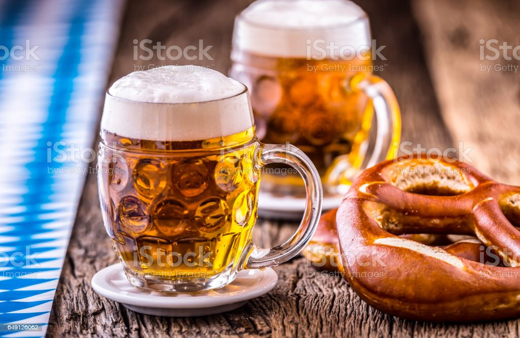 Beer. Oktoberfest.Two cold beers and pretzel. Draft beer. But draft. Golden beer. Golden however. Two gold beer with froth on top. Cold draft beer in glass jars in a hotel pub or restaurant. Still life stock photo