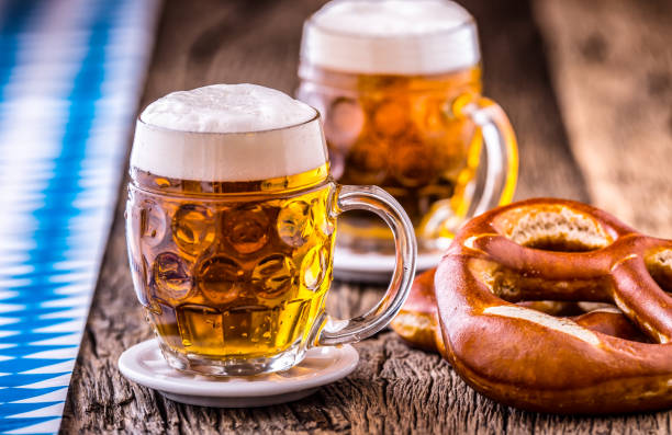 beer. oktoberfest.two cold beers and pretzel. draft beer. but draft. golden beer. golden however. two gold beer with froth on top. cold draft beer in glass jars in a hotel pub or restaurant. still life - german culture stock pictures, royalty-free photos & images