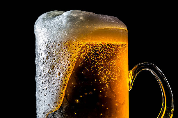 beer overflowing large glass with foam and bubbles isolated - overflowing stock photos and pictures