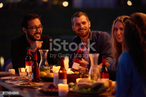 Positive young friends having conversation over beer, they resting at outdoor party