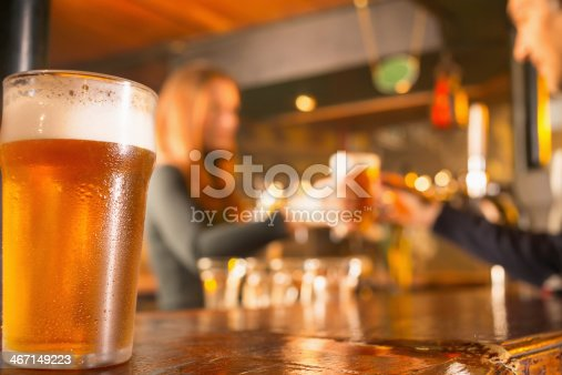 Ice Cold  Glass of  Beer , covered with water drops - condensation. Standing on wooden  counter at a bar. Foam on the beer looks real and perfect while the colors between the glass  fit perfectly with the contrast and shapes on the table.The grain and texture added. Very shallow DOF .