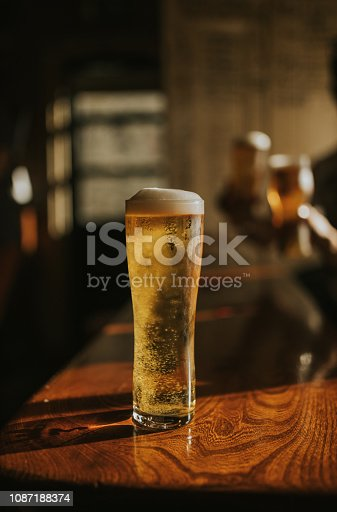 istock Beer pint on a wooden table at the pub 1087188374