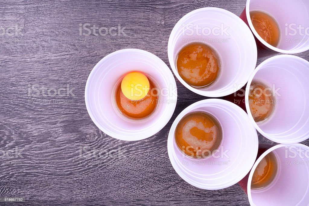 Beer pong game Red plastic cups arranged for playing Beer Pong isolated on wooden background. Above Stock Photo