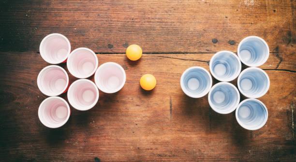 bier pong. plastic rode en blauwe kleur cups en ping pong ballen op hout, bovenaanzicht - beirut stockfoto's en -beelden