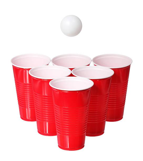 beer pong. red plastic cups and ball isolated - beirut stockfoto's en -beelden