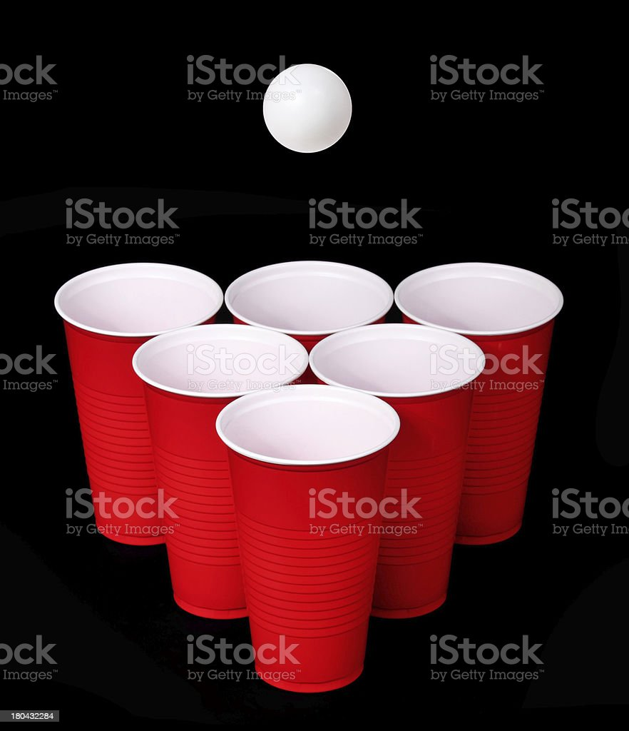 Beer pong. Red plastic cups and ball over black stock photo