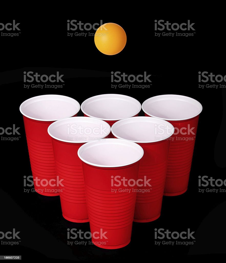 Beer pong. Red plastic cups, orange tennis ball over black stock photo