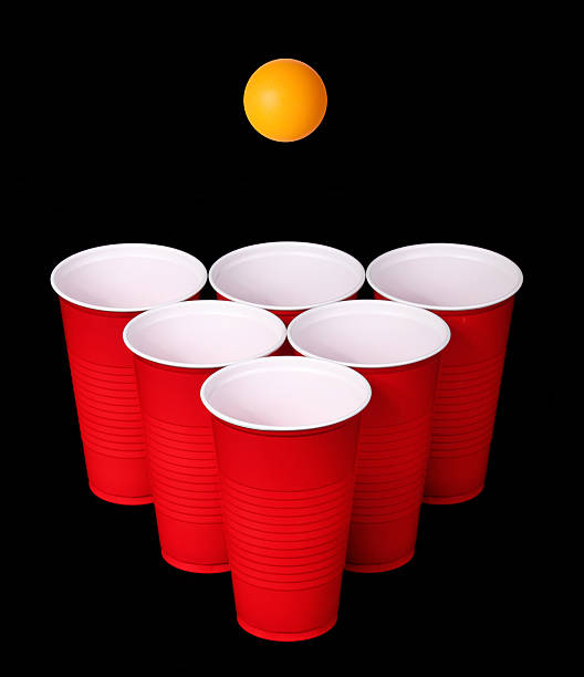 beer pong. red plastic cups, orange tennis ball over black - beirut stockfoto's en -beelden