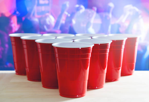 Beer pong tournament layout. Many red party cups in a nightclub full of people dancing on the dance floor in the background. Perfect for marketing and promotion for event. Plastic mugs on wooden table stock photo