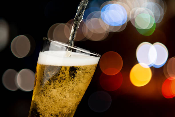 Beer pouring from bottle into glass on bokeh light night background drinking alcohol celebration concept design stock photo