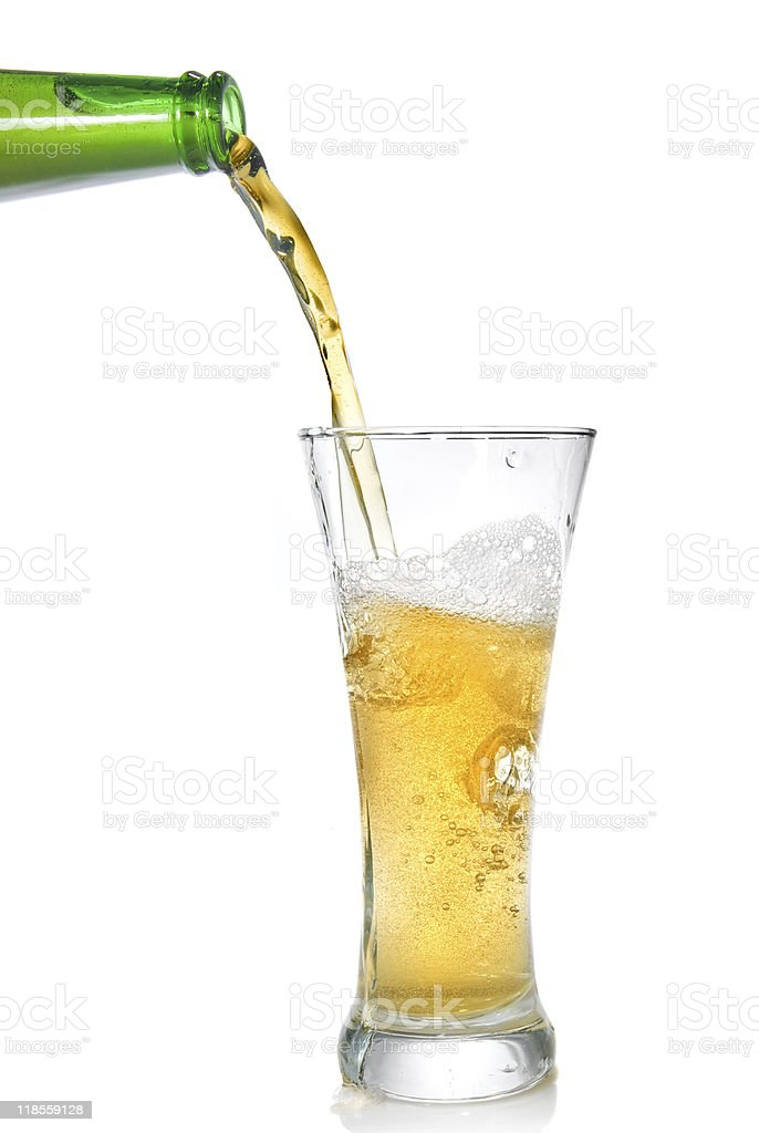 Beer pouring from bottle into glass stock photo