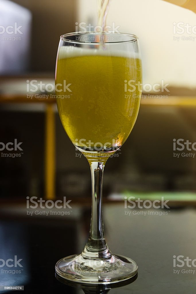 Beer pouring in to the wine glass in a bar royalty-free stock photo