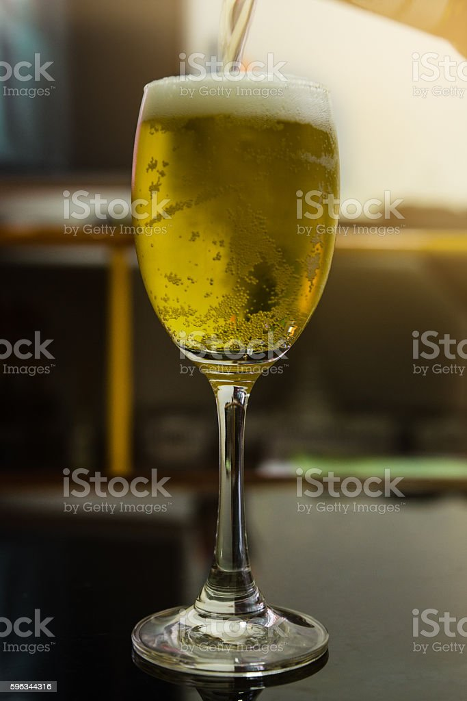 Beer pouring in to the wine glass in royalty-free stock photo