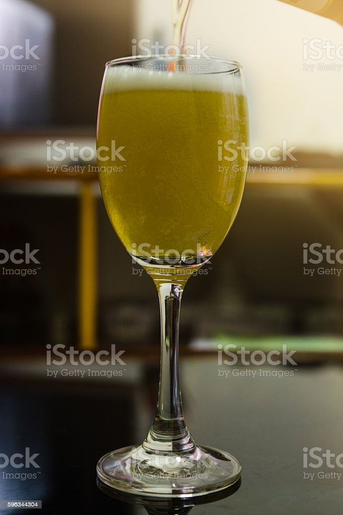 Beer pouring in to the wine glass Lizenzfreies stock-foto