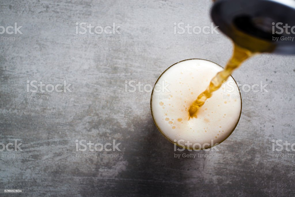 Beer pouring out of a can into a glass stock photo