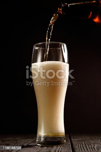 1073474208istockphoto beer pours into glass on black background 1166168703