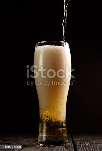 1073474208istockphoto beer pours into glass on black background 1168778995