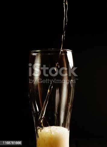 1073474208istockphoto beer pours into glass on black background 1168781666