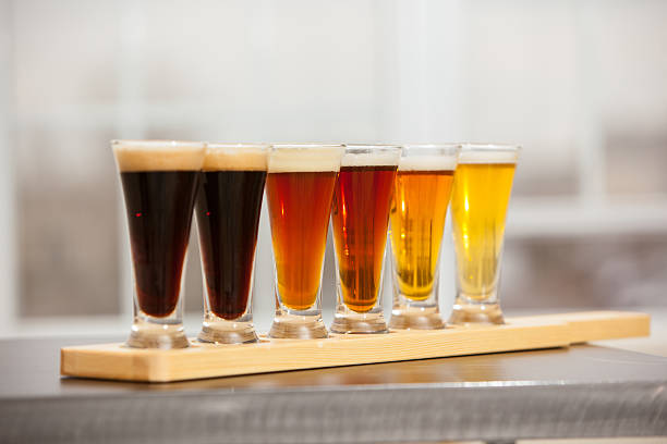 Beer samples lined up on a bar. stock photo