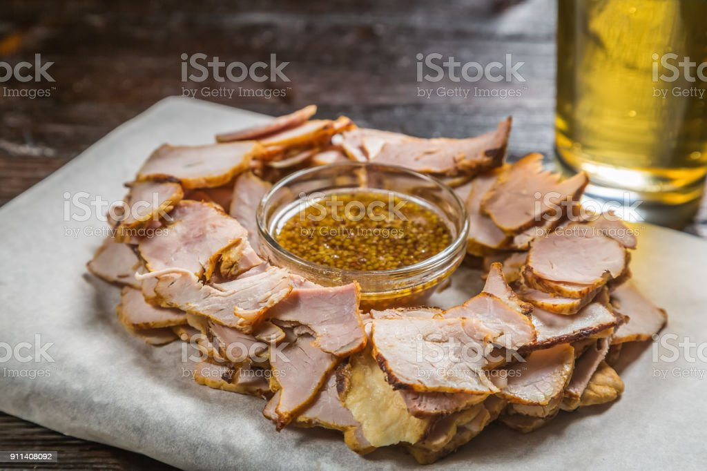 Beer snack of thinly sliced pieces of meat with a sauce of grainy mustard on the Board for filing is covered with a sheet of parchment. stock photo