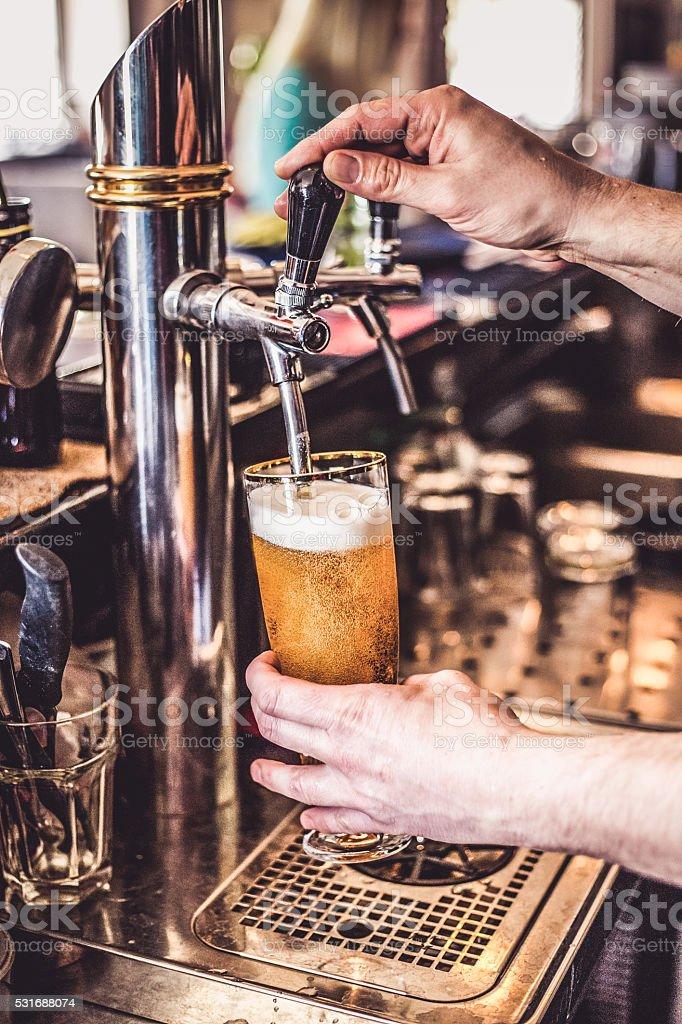 Spillatore per la birra versare un bicchiere di birra alla spina - foto stock