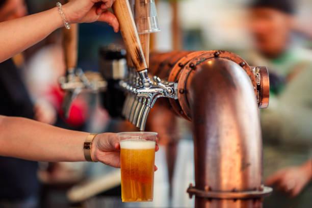 플라스틱 컵에 맥주를 두드리는 - 맥주 공장 뉴스 사진 이미지