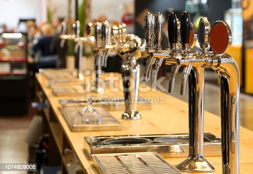 istock beer taps lined up on the counter of a pub 1074809008