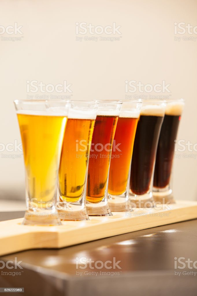 Beer tasters lined up on a bar. stock photo