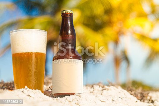 Beer under the palm tree on a beach