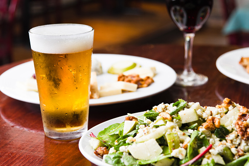 Icy cold beer with salad and appetizer dishes and red wine in a restaurant setting.  Beer glass has been frozen and shows condensation on the outside and a nice large head on the top.
