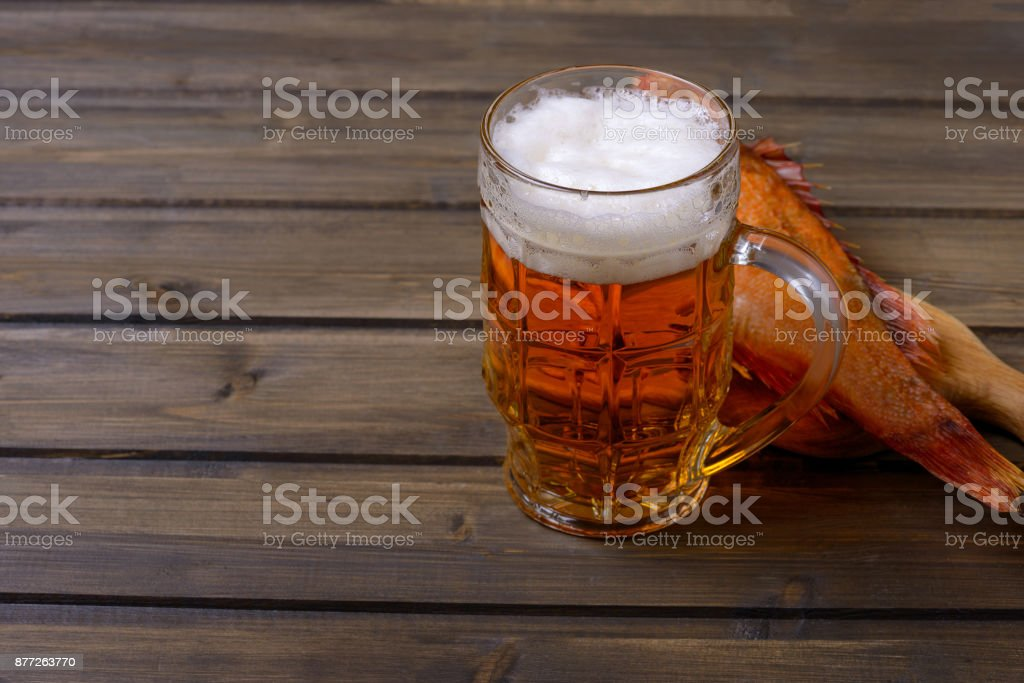 Beer with foam and fish on wooden table stock photo