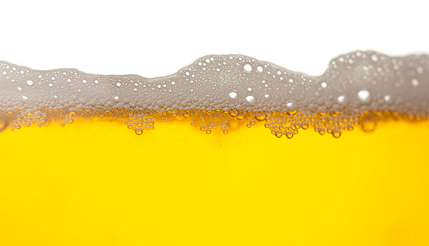 Beer with forth Close up light beer with forth. lager stock pictures, royalty-free photos & images