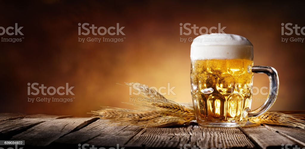Beer With Wheat On Wooden Table stock photo