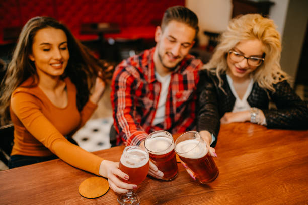 cervezas y vítores - lifestyle color background fotografías e imágenes de stock