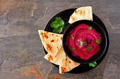 Beet hummus dip with pita bread on a black plate, above view on a dark background