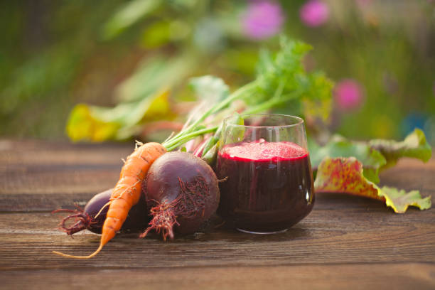 beet-Carrot juice in glass on  table beet-Carrot juice in glass on wooden table vegetable juice stock pictures, royalty-free photos & images