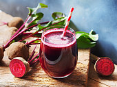 Beetroot juice in a glass and fresh organics beetroot on rustic wooden table for refreshing drinks concept.