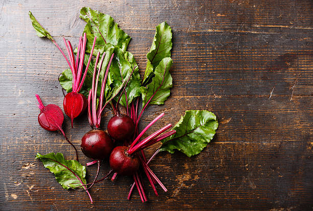 Beetroot on wooden background Red Beetroot with herbage green leaves on wooden background beet stock pictures, royalty-free photos & images