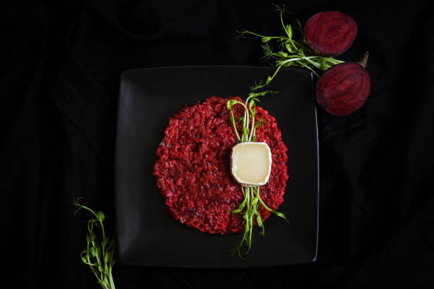 Beetroot risotto with goat cheese and green sprouts. stock photo