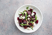 beetroot salad with blue cheese, arugula and walnut in a white plate on gray background, top view