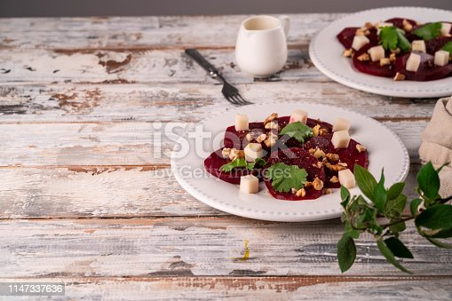 beetroot salad with goats cheese and walnuts on a white plate, on a wooden backdrop