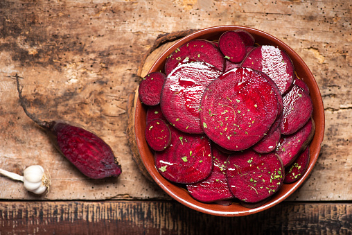 Beetroot salad with parsley in a bowl on a rustic wooden table