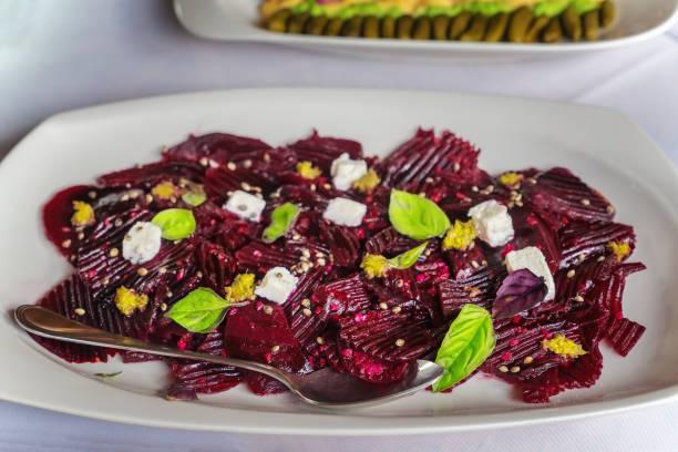 rote beete scheiben mit feta-käse, basilikum und einem löffel. - carpaccio salat stock-fotos und bilder