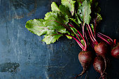 Bunch of beets on dark blue metal surface.