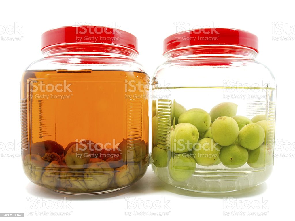 Before and after pickle Japanese plum liqueur in glass jar stock photo