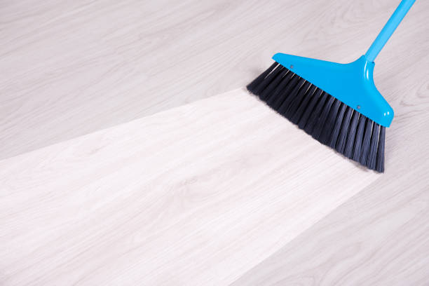 before and aftet cleaning concept - blue broom sweeping floor stock photo