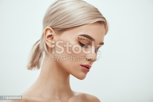Before facial surgery. Side view of pretty young blonde woman with sketch on her face standing against grey background. Plastic surgery concept. Healthcare. Beauty concept.