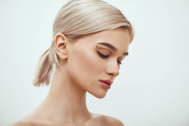before facial surgery. side view of pretty young blonde woman with sketch on her face standing against grey background - eyelid stock pictures, royalty-free photos & images